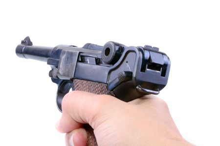 luger: Hand holding a German Luger pistol isolated on a white background Stock Photo