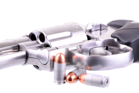38 caliber: Macro shot of a revolver and bullets over white