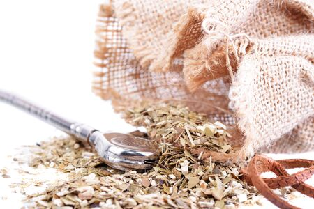 mate infusion: Close up of a bag with mate tea pouring out and a silver bombilla Stock Photo