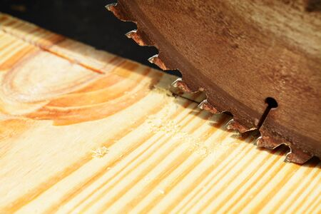 blades: Macro shot of a table saw blade over a pine wood board Stock Photo
