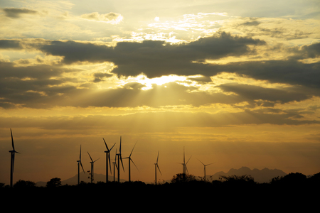 wind down: Wind turbines as silhouettes against a beautiful sunset with sun beams shining down
