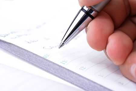 appointment book: Man holding a pen over an appointment book Stock Photo