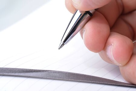 appointment book: Macro shot of a hand holding a pen over an appointment book Stock Photo