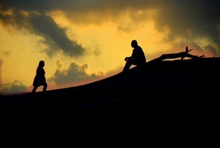 Silhouettes of a woman walking towards a man that is sitting at a beach during  sunset