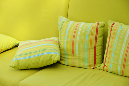 Close up shot of a green terrace sofa and pillows