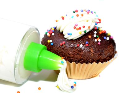 Macro shot of a chocolate cupcake with sprinkles and a cream decoration dispenser Stock Photo