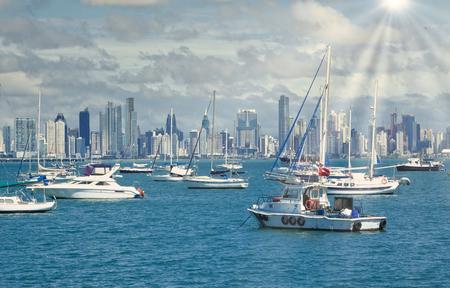 Boats and Yachts in the Bay of Panama with the Skyline of Panama City in the background with sunrays shining