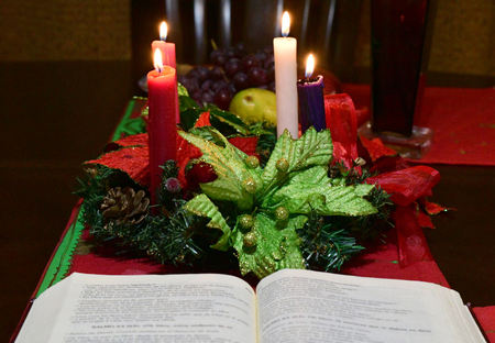 Close up of a traditional christmas table with candles, the holy book and an Advent Crown