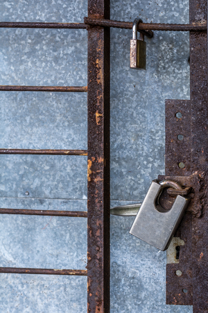 keep gate closed: Old padlock on a metal door with grill