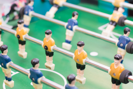 medium body: Players of the game of Foosball in orange and blue color Stock Photo