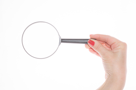Womans hand with nail polish, holding a magnifying glass on a white background