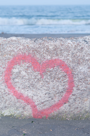 forgiven: Red heart spray painted on a wall in the background of beach Stock Photo