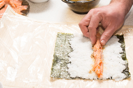 Cooking sushi at home with nori, salmon, rice photo