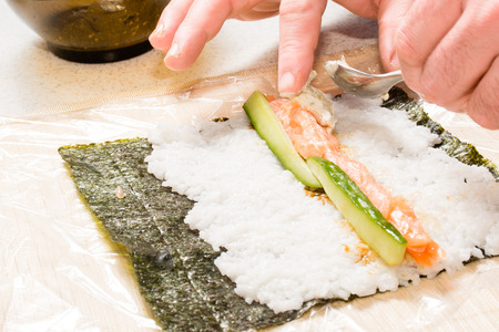 Cooking sushi at home with nori, salmon, avocado, rice and cucumber. photo