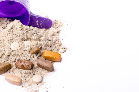 plastic scoop: Whey protein powder in scoop with vitamins and violet plastic shaker Stock Photo