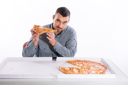 mealtime: Young man eating pizza with mozzarella and gouda on a white background Stock Photo