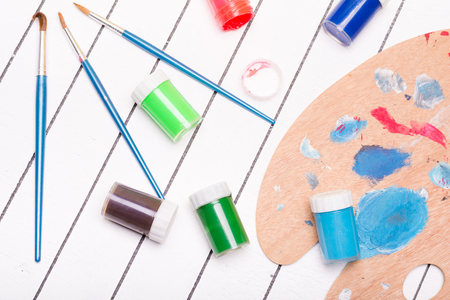 tempera: Watercolor and tempera with paint brushes on a white wooden background Stock Photo