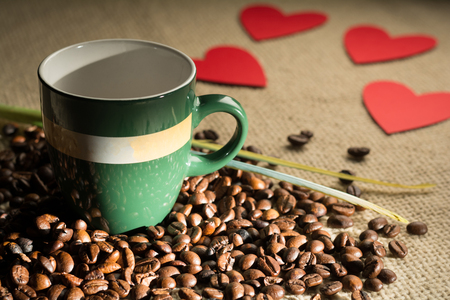 dispersed: Cup of coffee with beans and hearts dispersed paper