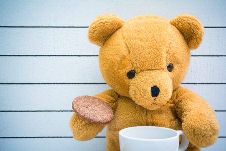 teddy bear baby: Teddy bear drink milk with biscuits on a wooden background Stock Photo