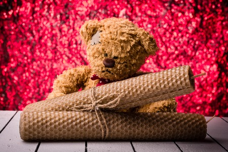 vax: Beeswax candles and teddy bear with ribbon of natural material background bukeh