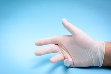 utiles de aseo personal: Mano masculina en guante médico sobre fondo azul