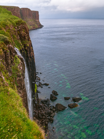 Beautiful view from Kilt Rock and Mealt Falls Viewpoint. Typical overcast weather for Isle of Skye. Big waterfall, dramatic cliffs and deep blue sea on a windy summer day.