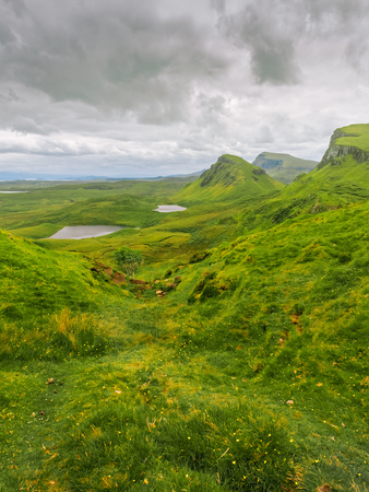 Green hills on the Isle of Skye as seen from Quiraing landslip. Two small lakes at the background with small yellow flowers in front. Overcast weather with grey clouds on a windy summer day. Stock Photo