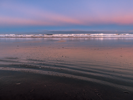 View of the ocean beach at low tide just before the sunrise with blurred waves and clouds in the background. Picture taken at Manzanita Beach, Oregon. Dark sand formations are seen in the foreground.