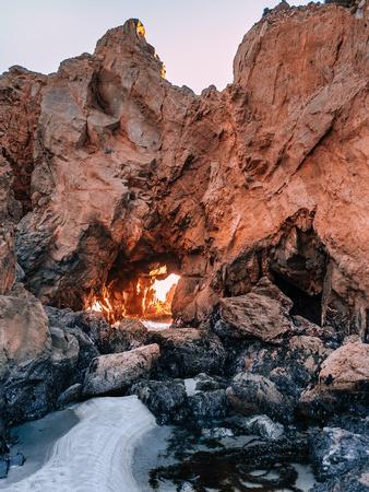 Disparo vertical del famoso acantilado con Keyhole Arch en Pfeiffer Big Sur State Park, en la costa del Pacífico de California. La luz del sol poniente entra por una abertura en la roca.