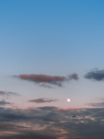 Four-engine commercial jet airliner flying at low altitude in the evening sky just below the bright full moon. Pastel colors with dark grey clouds, glowing red at sunset. Copy space at the top.