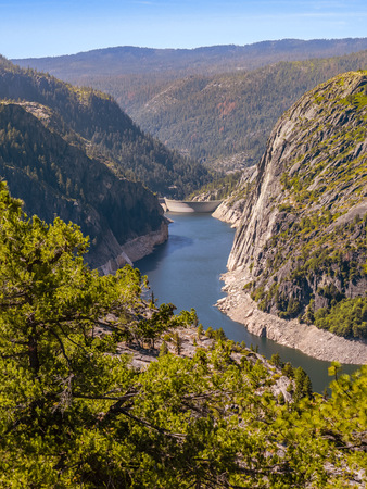 Awesome view to the picturesque Donnell Reservoir on the Middle Fork Stanislaus River in Tuolumne County, California. Lake surrounded by granite rocks with concrete arch dam is seen at the background. Фото со стока