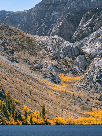 Colorful autumn vegetation on the lakeshore at the bottom of a rocky mountain slope. Deep blue waters of Convict Lake in the Eastern Sierras. A small boat in the distance. Shot taken in early October.