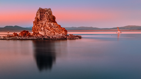 Tufa rock glows red and orange by the setting sun as its silhouette and clear pastel sky are reflecting on the blue water of Mono Lake, California. Copy space at the bottom, mountains on the horizon.