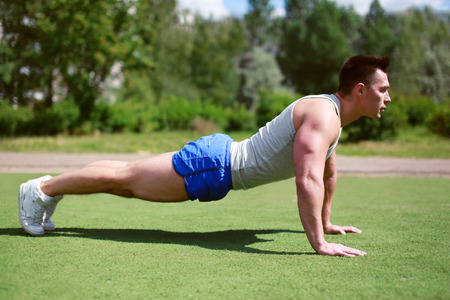 Fitness, workout, sport - concept. Sportsman push ups\ outdoors