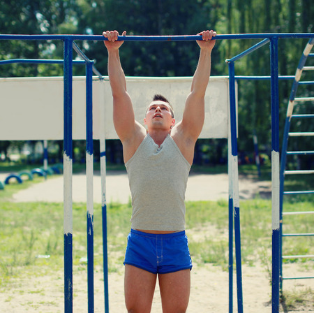 Workout, sports man pulls on the horizontal bar photo
