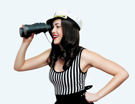 Beautiful girl in the image of a sailor, charming smiling brunette, looking through binoculars. pin up style