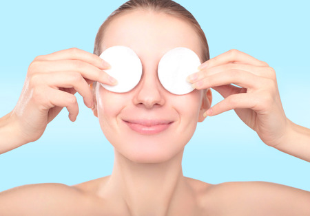 female eyes: Beautiful smiling woman with cotton pads