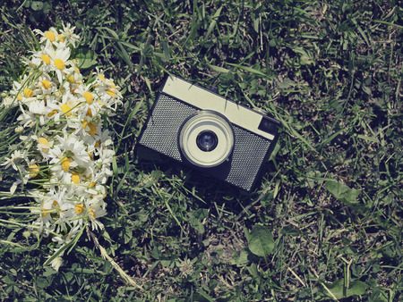 Vintage old camera and flowers photo