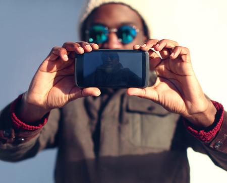 hombres negros: Tecnología y concepto de la gente - hombre africano con estilo moderno hace Autofoto, vista delantera de la pantalla