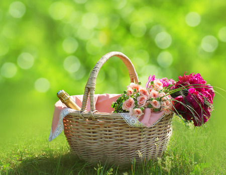 romance background: Romance, love and valentines day concept - sweet basket with bouquet of flowers on the grass. Spring fresh relax background Stock Photo