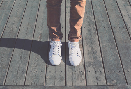 Fashion hipster cool man with white sneakers, soft vintage toned colors