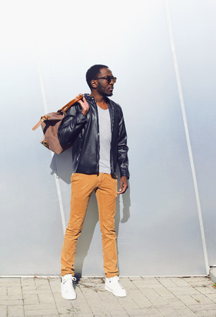 Outdoor fashion portrait of handsome african man in black leather jacket with bag standing against the shiny metal wall