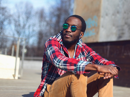 urban style: Outdoor fashion portrait of stylish young african man listens to music and enjoys freedom in the city, wearing a plaid hipster red shirt and sunglasses