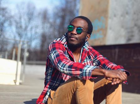 sunglasses: Retrato de la moda al aire libre de estilo hombre africano joven escucha la música y disfruta de la libertad en la ciudad, que llevaba una camisa roja a cuadros inconformista y gafas de sol