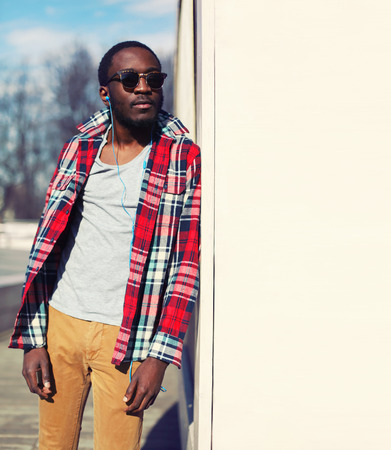 Outdoor fashion portrait of stylish young african man listens to music and enjoys freedom, wearing a plaid hipster red shirt and sunglasses, posing near urban white wall for background, copy space
