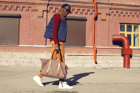 stylish: Street fashion concept - handsome stylish african man walks in the city Stock Photo
