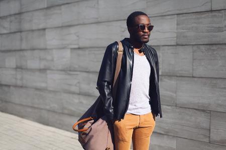 Street fashion concept - stijlvolle knappe Afrikaanse man die in de stad tegen een grijze getextureerde muur