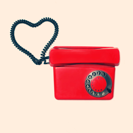 old phone: Red old retro rotary phone with heart shape of wire, vintage colors photo