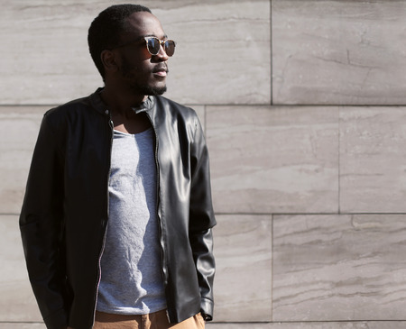 Fashion portrait of stylish young african man wearing a sunglasses and black rock leather jacket over textured background
