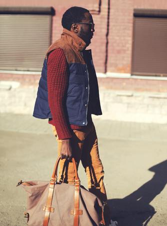 modelos hombres: Moda hombre guapo africano elegante con una chaqueta de chaleco, su�ter y bolsa de caminar en la noche de la ciudad, colores de la vendimia Foto de archivo